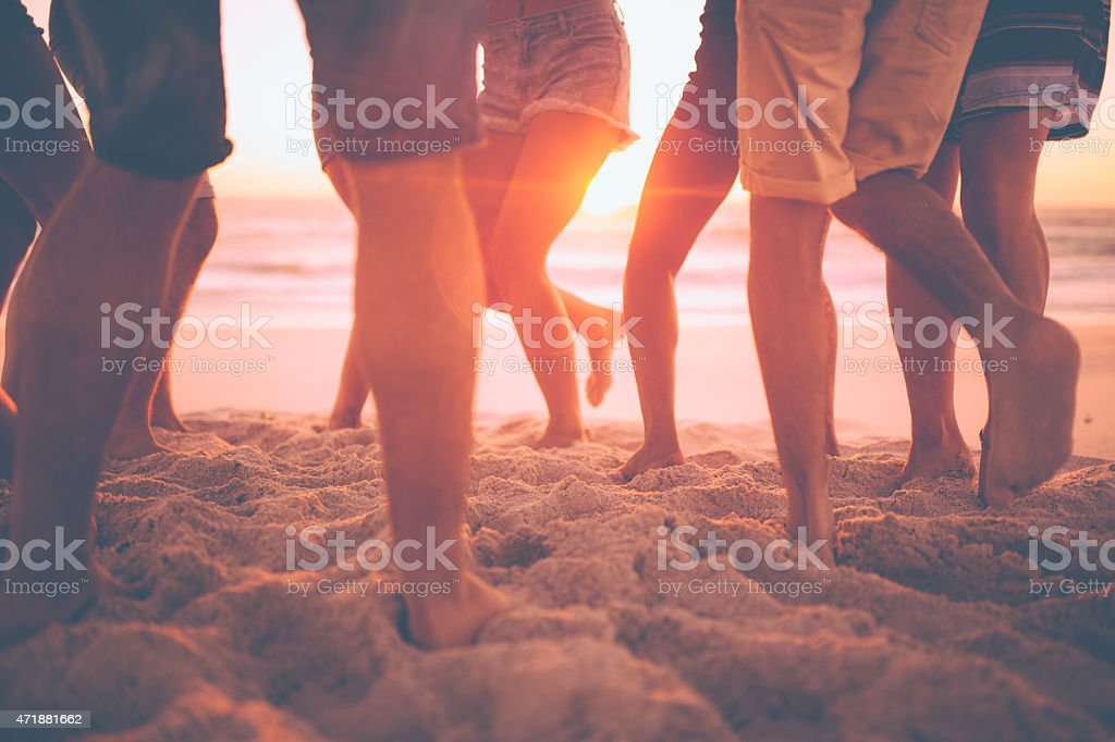 Legs of youth dancing on the beach at sunset stock photo