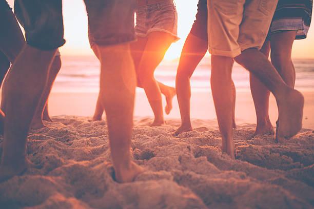 Gambe dei ragazzi ballare sulla spiaggia al tramonto - foto stock