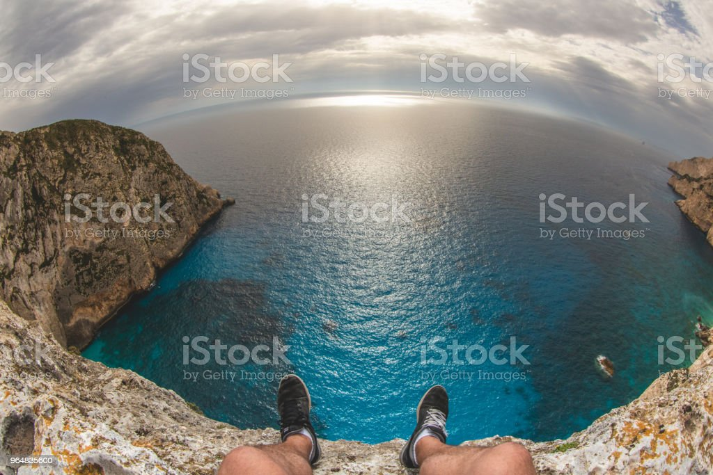 Legs over the cliff edge, Zakynthos, Greece royalty-free stock photo