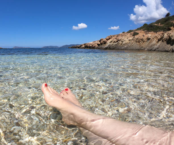 legs relaxing in the beach of sardinia - woman leg beach pov stock photos and pictures