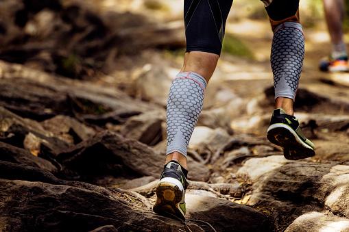 legs runner in compression calf sleeve running uphill on rocks