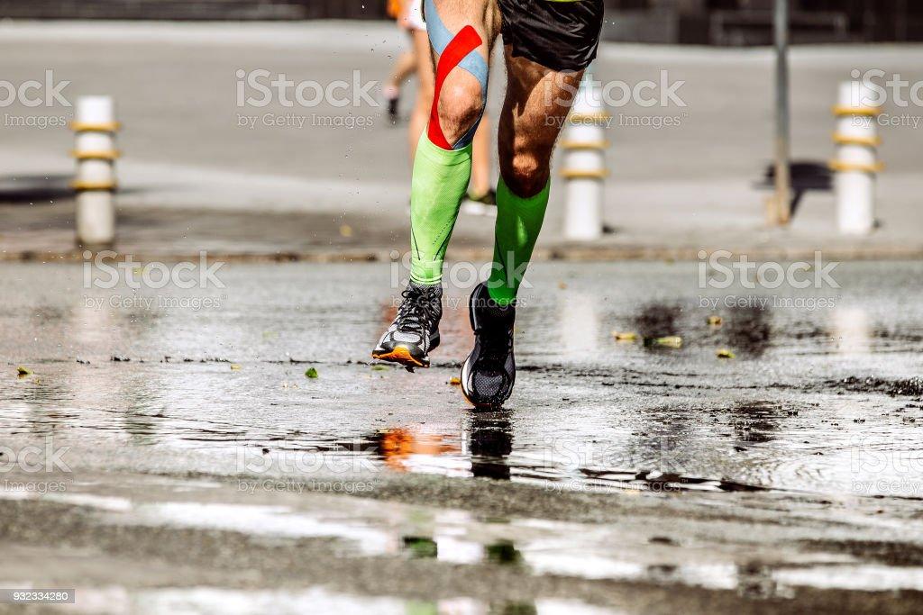 e0ecc38d7e Legs runner man with kinesio tape and compression socks - Stock image .