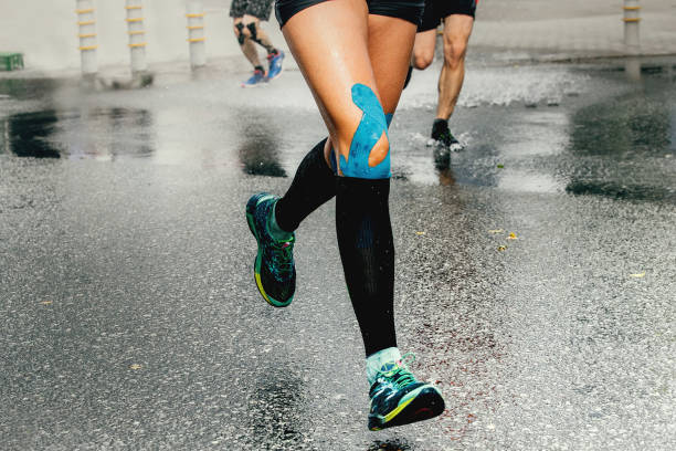 legs runner woman with kinesio tape and compression socks stock photo