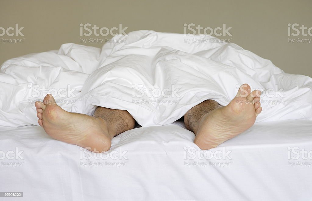 Legs sticking out of a duvet royalty-free stock photo
