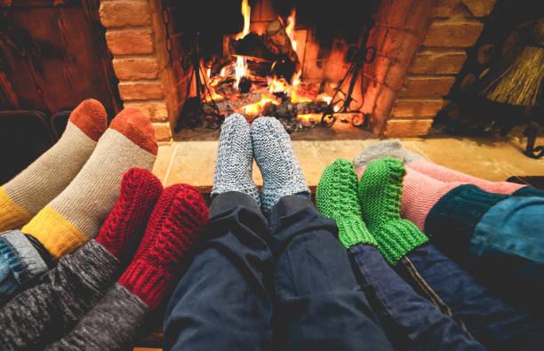 vista de las piernas de la familia feliz usando calcetines calientes frente a la chimenea - invierno, amor y concepto acogedor - enfoque en calcetines de lana gris centro - invierno fotografías e imágenes de stock