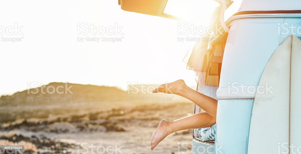 Legs view of happy surfer girl inside minivan at sunset - Young woman having fun on summer vacation - Travel,sport and nature concept - Focus on feet - Warm contrast filter stock photo