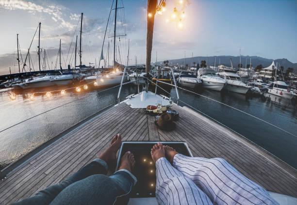 Beine Ansicht des Senior-Paares mit Urlaub auf Segel Vintage Boot - 60er Jahre trendige Menschen genießen einen romantischen Urlaub - Reisen, Luxus, fröhliche ältere Lebensstil und Liebe Konzept - Fokus auf Füße – Foto