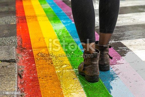Female legs walking on rainbow crosswalk in Gay parade.