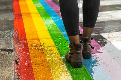 Legs walking on Gay rainbow crosswalk.