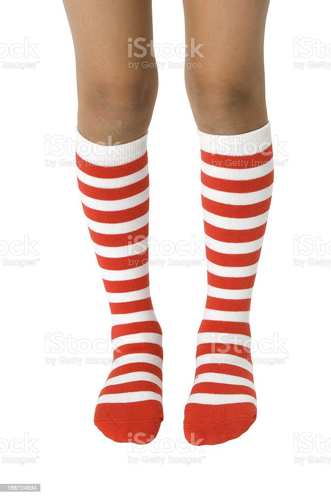 Legs wearing long red striped socks on a white background. stock photo
