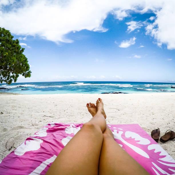 Legs with fake spray tan on sun lounger on tropical beach with pink towel at Lefaga, Upolu Island, Samoa, South Pacific stock photo