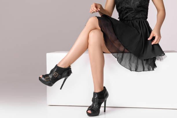beine frau trägt high heels schuhe auf der bank sitzen. - schwarze hohe schuhe stock-fotos und bilder