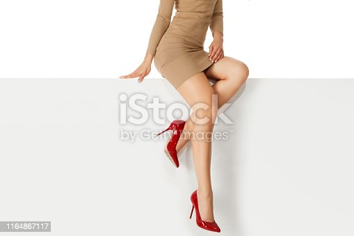 Beautiful legs woman wearing beige dress and red high heels shoes sitting on white bench. copyspace.