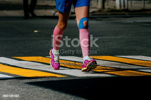 Ekaterinburg, Russia - August 7, 2016: legs women athletes in compression socks and taping knee during Marathon Europe-Asia