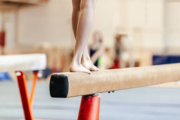piernas mujeres gimnastas ejercicios en el haz de equilibrio - foto de stock