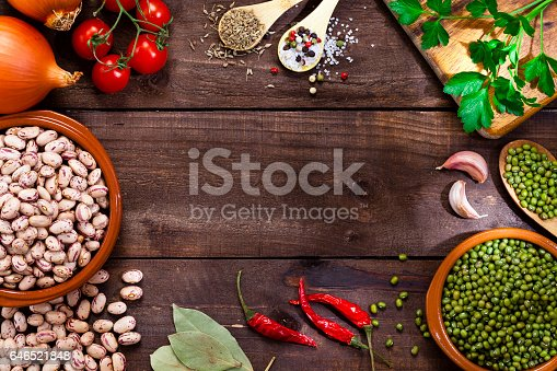 Top view of a rustic wood table with legumes and ingredients for cooking all around the border leaving a useful copy space at the center of the table. DSRL studio photo taken with Canon EOS 5D Mk II and Canon EF 100mm f/2.8L Macro IS USM