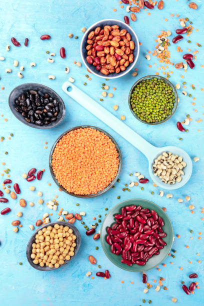 Legumes, overhead shot on a blue background. Vibrant pulses including colorful beans, lentils, chickpeas, a flatlay composition stock photo