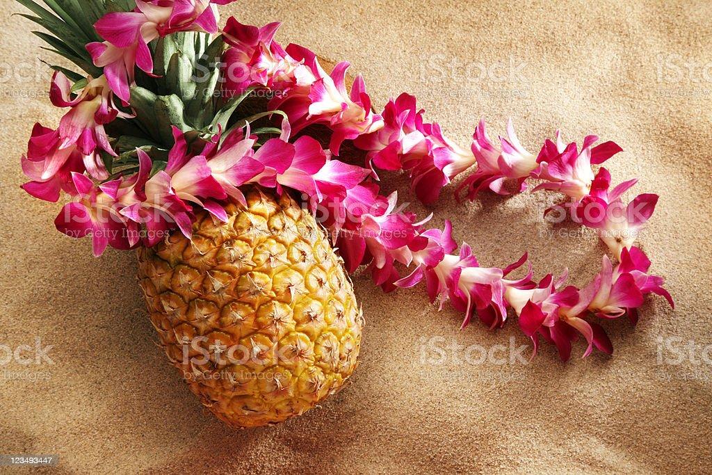 lei on pineapple at the beach stock photo