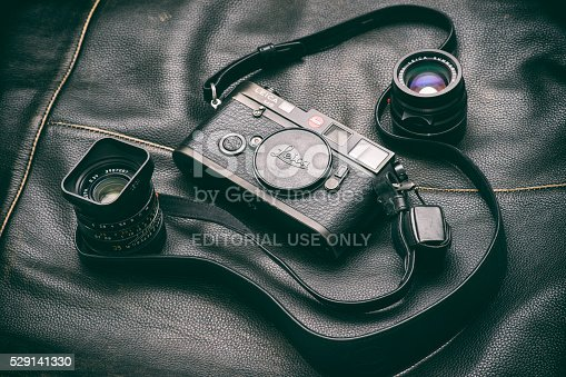 Bucharest, Romania - May 6, 2016: Image of a black Leica M6 camera body with a Summicron 35 mm and a Summarit 50 mm lenses sitting on a black leather surface. Bucharest, Romania, May 6, 2016.