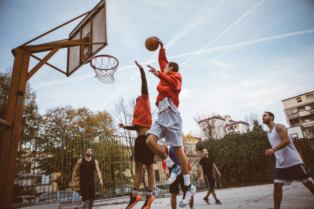 Leisure activities Group of male friends playing basketball at city court courtyard stock pictures, royalty-free photos & images