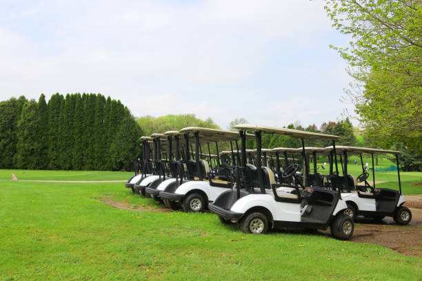 Leisure and outdoor activity background with a golf course. Spring landscape with cloudy blue sky over the green grass field and rows of carts at the golf course. Healthy lifestyle concept. dane county stock pictures, royalty-free photos & images