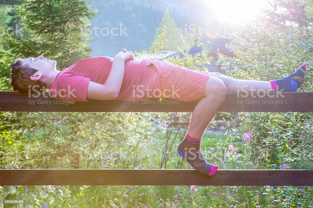 Leisure and relaxing outdoors summer evening, teenage boy laying down. royalty-free stock photo