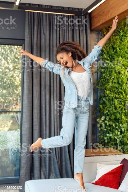 Leisure at home young african woman jumping on sofa hands aside picture id1193200120?b=1&k=6&m=1193200120&s=612x612&h=xlvj6nvecixr1csagwsq5 ypo6xnkvwdst8y w0psny=