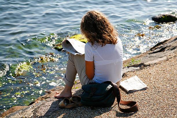 leisure by the sea - newspaper beach stockfoto's en -beelden