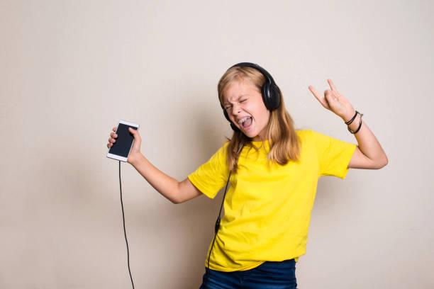Freizeitkonzept. Glückliche vor-Teenager oder Teenager-Mädchen in Kopfhörern hören Musik von Smartphone und tanzen in ihrem Zimmer. – Foto