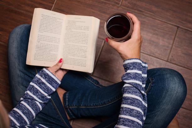 Freizeit, Getränke, Bildung und Lifestyle-Konzept. Frau sitzt auf dem Boden, Holdind Buch und Glas Rotwein. Frau mit einem Glas Wein und lesen. – Foto