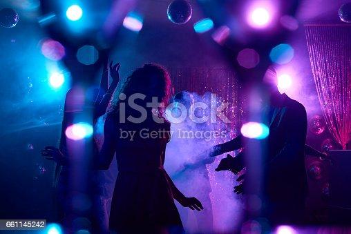 Young people dancing in smoke and enjoying nightlife