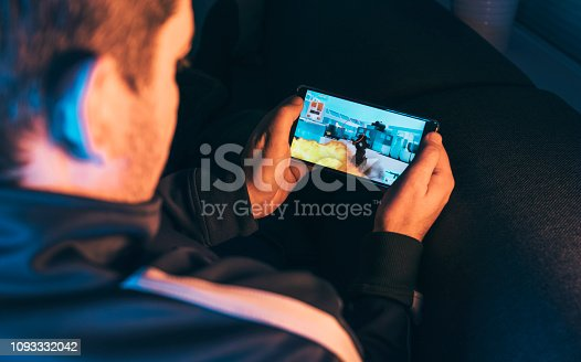 Man holds mobile in his hands and play a mobile action game. It features a crosshair and a machine gun. He sits at home at night playing the game.