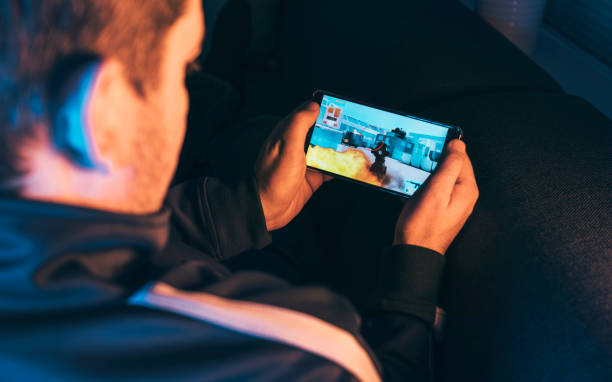 Leisure gamer plays action video game on mobile phone at night Man holds mobile in his hands and play a mobile action game. It features a crosshair and a machine gun. He sits at home at night playing the game. leisure games stock pictures, royalty-free photos & images