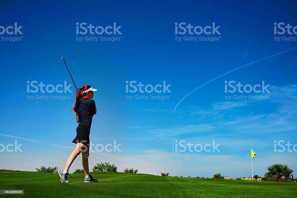 side view of woman hitting golf ball, enjoying great game...