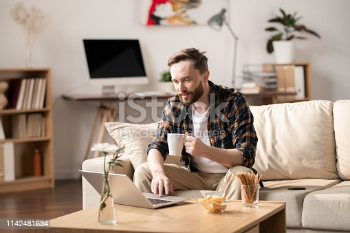 Young casual man with mug of hot drink looking at laptop display while sitting on sofa, watching online video and having snack