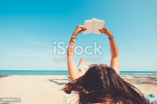 Leisure in summer - Young woman lying on a tropical beach, relax with book. Blue sea in the background. Summer vacation concept. vintage color tone.