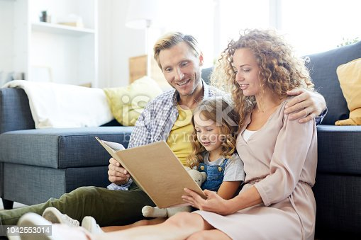 Young family of three reading book of stories while sitting on the floor by sofa at leisure