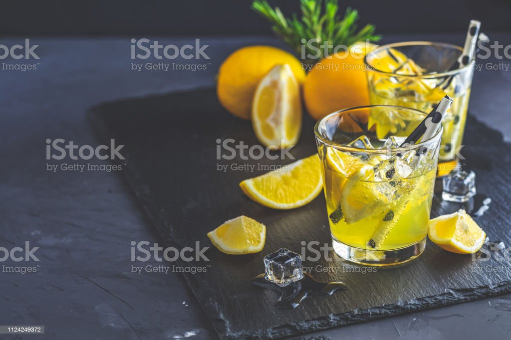 Lemon alcohol drink cocktail with ice, lemon and rosemary stock photo