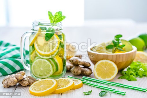 Front view of a mason jar filled with lemon and ginger infused water shot on white table. Some lemon slices, ginger roots and two green and white drinking straws complete the composition. Predominant colors are yellow, green and white. High resolution 42Mp studio digital capture taken with Sony A7rii and Sony FE 90mm f2.8 macro G OSS lens