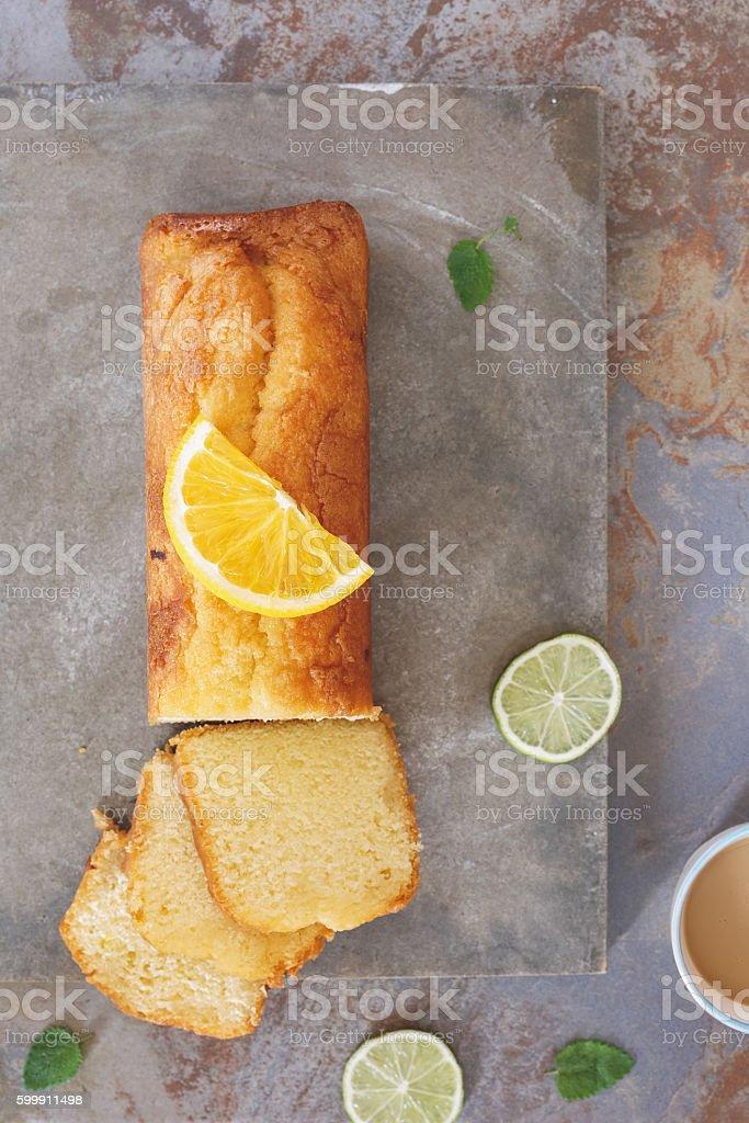 Lemon and orange cake, partly sliced stock photo