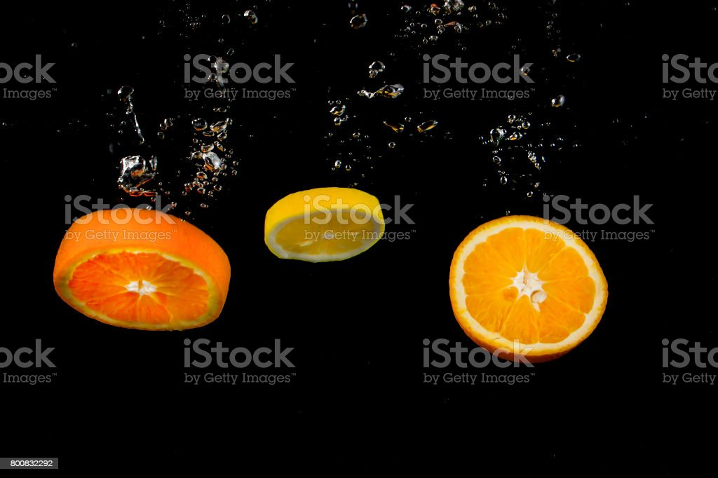 lemon and orange splashing in water on dark background with bubbles...