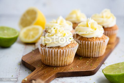 Lemon and poppy seed cupcakes with cheese cream frosting and lemon and lime zest on a cutting board