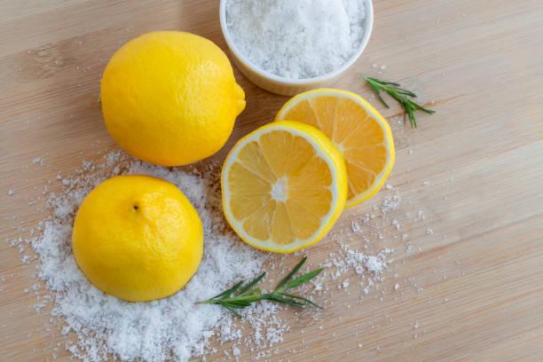 레몬과 바다 소금. 바디 스크럽과 스파 관리를위한 나무와 로즈마리 배경에 레몬 재료와 유기농 화장품 뷰티 트리트먼트. 스톡 사진