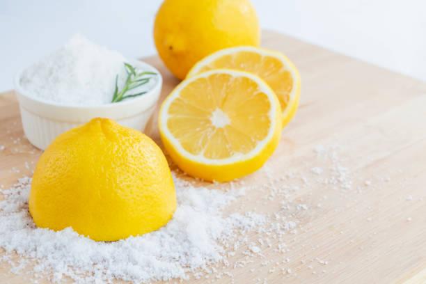 레몬과 바다 소금 - 바디 스크럽과 스파 관리를위한 나무와 로즈마리 배경에 레몬 재료와 유기농 화장품 뷰티 트리트먼트. 스톡 사진