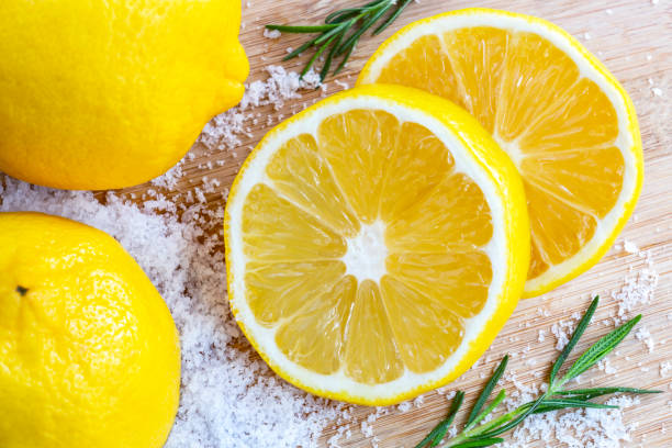 레몬과 바다 소금-바디 스크럽과 스파 케어에 대 한 나무와 로즈마리 배경에 레몬 재료로 유기농 화장품으로 치료. 스톡 사진