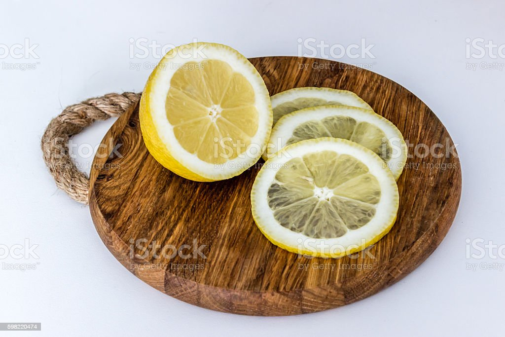 Lemon and slices on cutting board on light background foto royalty-free