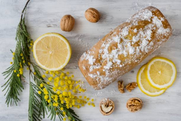 lemon cake with nuts on a wooden white surface, a twig of mimosa flowers - mimosa cake foto e immagini stock