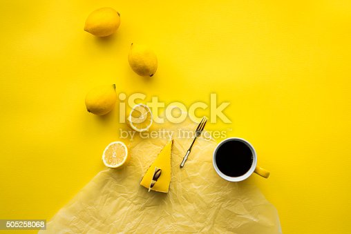 Lemon cheesecake, fresh lemons and black coffee on yellow background.