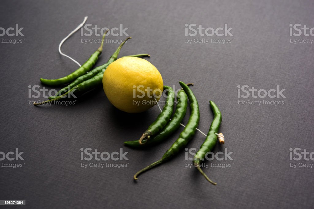 lemon chilies hanging - Indian superstitious lemon and green chillies tied with thread and tied on doors at home or shop to avoid any bad fortune also known as totka or nazar battu stock photo
