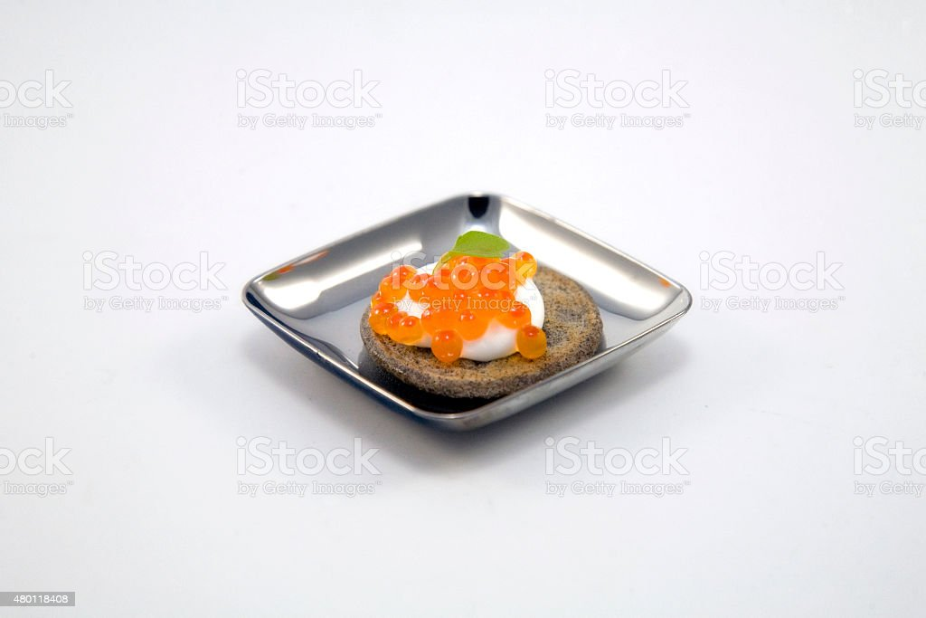Lemon Creme Blini with Trout Caviar Appetizer stock photo